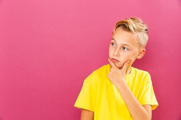 Niño pequeño pensando pose con espacio de copia