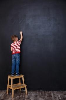 Niño pequeño de pie sobre una silla y dibujo