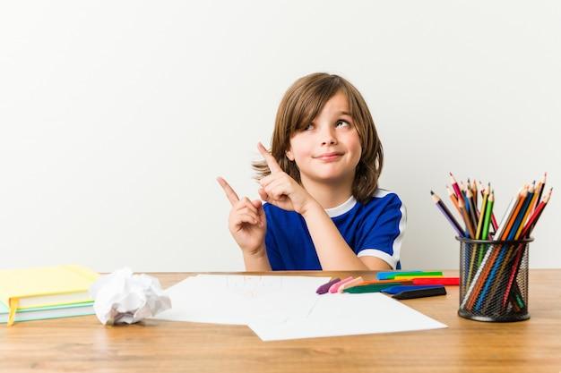 Niño pequeño pintando y haciendo los deberes en su escritorio sorprendido.