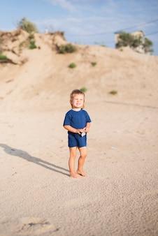Niño pequeño en la playa caminando en la playa
