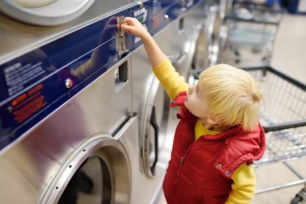 Niño pequeño pone monedas en la secadora en la lavandería pública