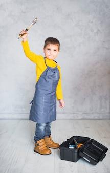 Niño pequeño, posición, con, llave inglesa