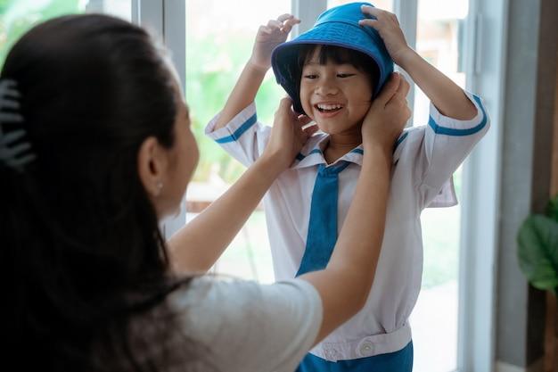 Niño pequeño preparándose para la escuela en la mañana con mamá