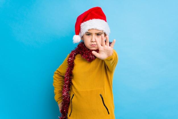 Niño pequeño que celebra el día de navidad que lleva un sombrero de santa aislado que se coloca con la mano extendida que muestra la señal de stop, previniéndole.