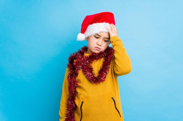 El niño pequeño que celebraba el día de navidad que llevaba un sombrero de santa aisló cansado y muy soñoliento manteniendo la mano en la cabeza.