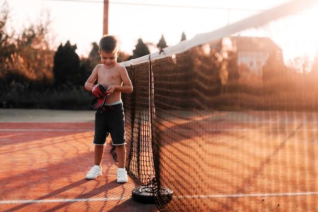 Niño pequeño que se coloca en patio del tenis y que pone guantes en sus manos. preparándose para el entrenamiento externo.