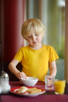 Niño pequeño que come el desayuno sano en restaurante del hotel. comida sabrosa en casa.