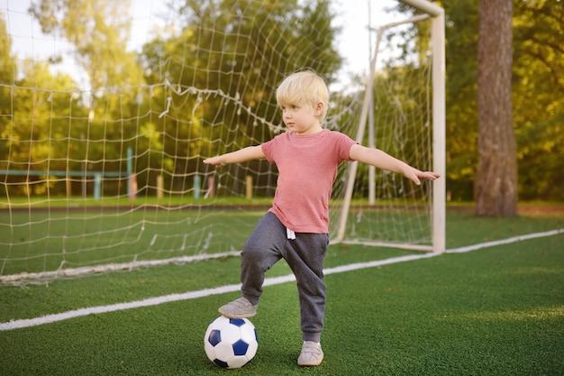 Niño pequeño que se divierte jugando un fútbol / partido de fútbol en día de verano.