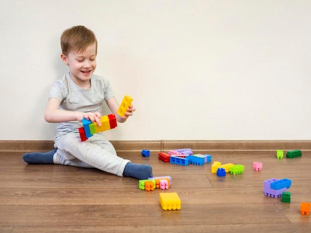 Niño pequeño que juega con los bloques coloridos