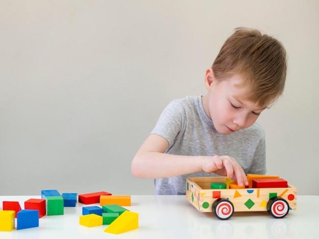 Niño pequeño que juega con el coche de madera
