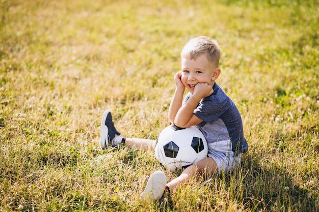 Niño pequeño que juega a fútbol en el campo