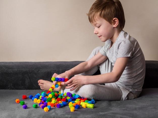 Niño pequeño que juega con el juego colorido en un sofá