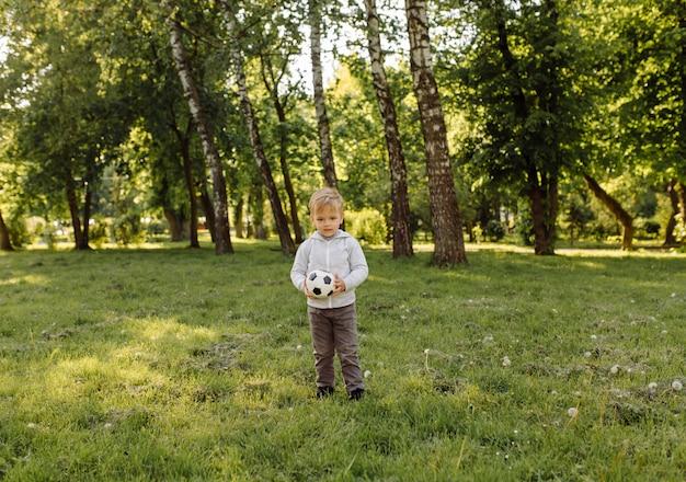 Niño pequeño que juega la pelota de fútbol al aire libre