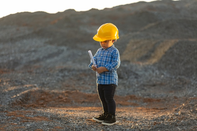 Niño pequeño que lleva un casco, concepto de sueño, quiere ser un futuro ingeniero.