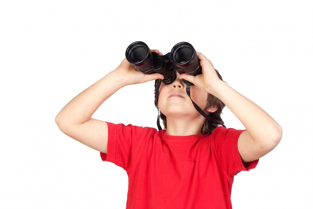 Niño pequeño que mira a través de los prismáticos aislados en el fondo blanco