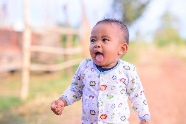 Niño pequeño que muestra la lengua.