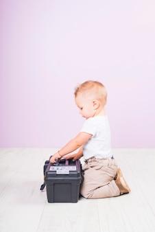 Niño pequeño que se sienta con la caja de herramientas en piso
