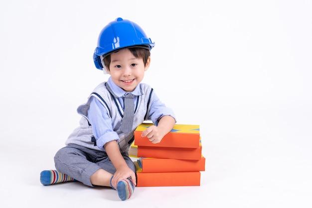 Niño pequeño que se sienta cerca del libro de la pila en blanco