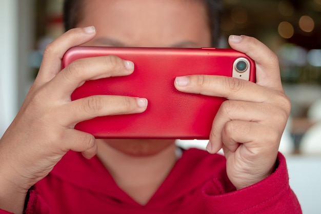 Niño pequeño que sostiene smartphone en posición horizontal. juego para niños, navegando en línea, aprendiendo.