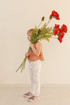 Niño pequeño que sostiene el tiro completo de las flores