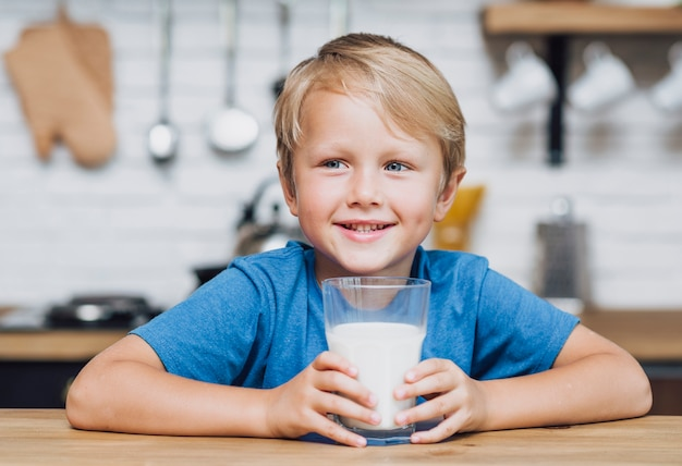 Niño pequeño que sostiene un vaso de leche