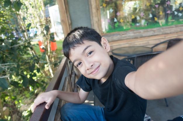 Niño pequeño que se toma selfie tiempo de verano al aire libre