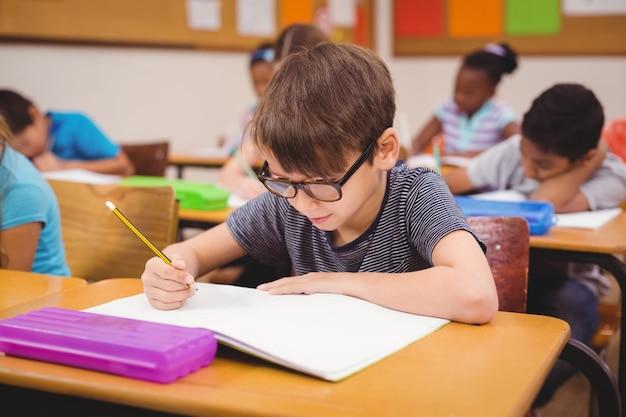 Niño pequeño que trabaja en su escritorio en clase