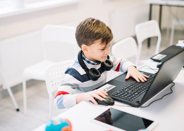 Un niño pequeño que usa la computadora portátil en el escritorio en el aula