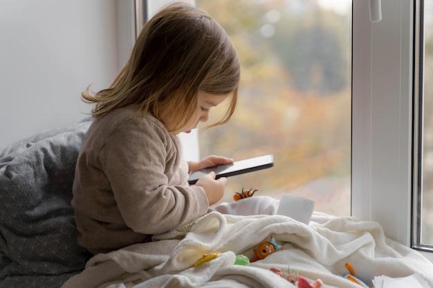 Niño pequeño que usa el teléfono en casa, toma fotos y juega