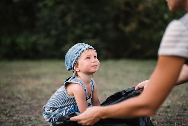 Niño pequeño quedándose con los padres afuera