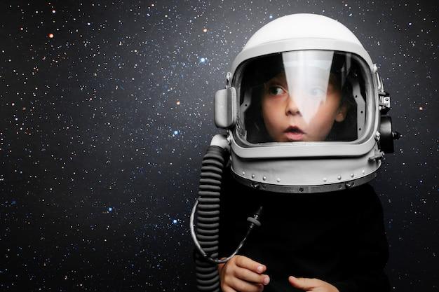 Un niño pequeño quiere volar un avión con un casco de avión