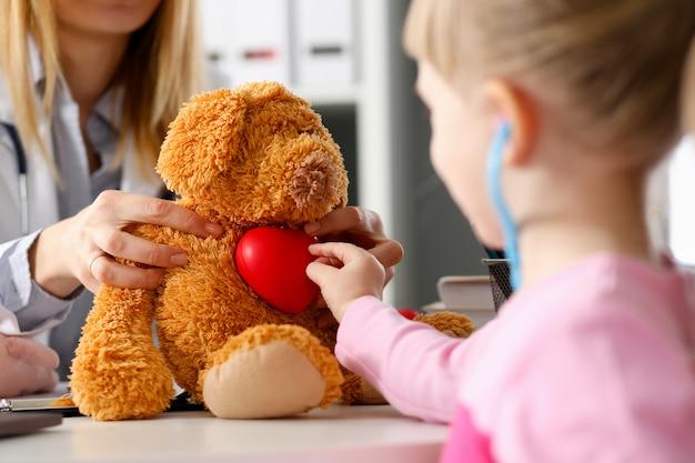 Niño pequeño en la recepción del pediatra escuchar