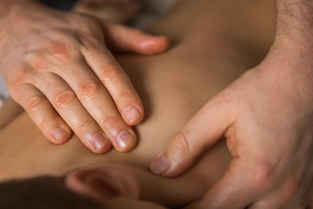 Niño pequeño se relaja con un masaje terapéutico. fisioterapeuta que trabaja con el paciente en la clínica a la espalda de un niño