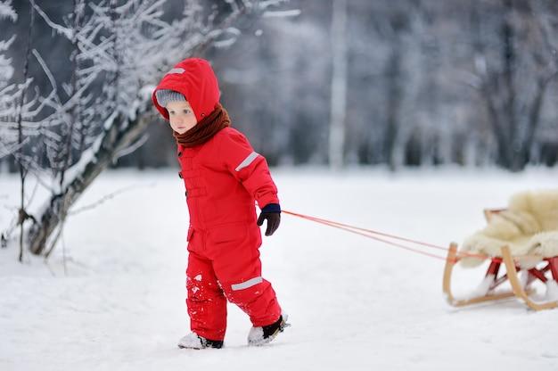 Niño pequeño en ropa roja del invierno con trineo largo. ocio activo al aire libre con niños en invierno.