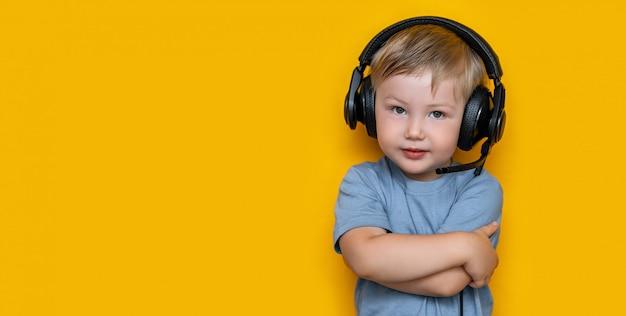 Niño pequeño rubio lindo hermoso tres años en auriculares negros del juego