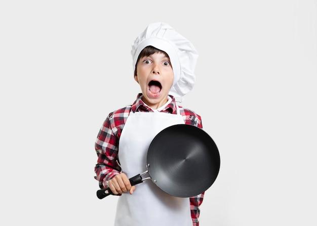Niño pequeño con una sartén sorprendido