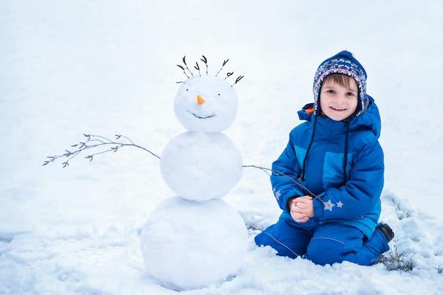 Niño pequeño sentado cerca del muñeco de nieve sonriente