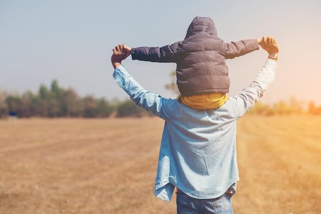 Niño pequeño está sentado en los hombros de su padre y pretendiendo un avión
