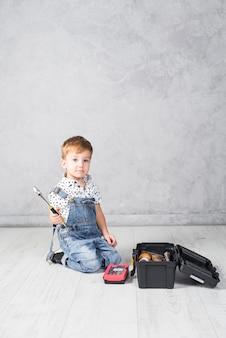 Niño pequeño, sentado, con, llave inglesa
