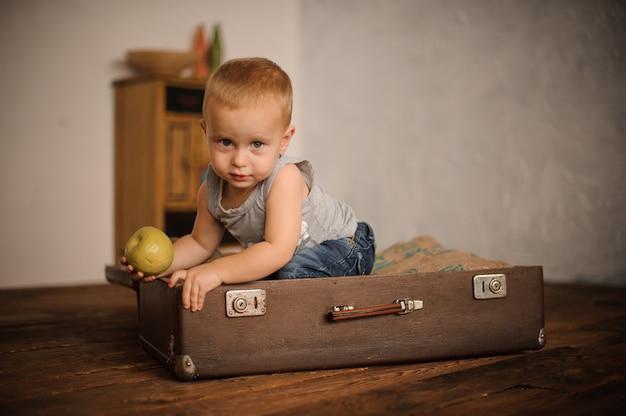 Niño pequeño sentado en la maleta y sosteniendo una manzana