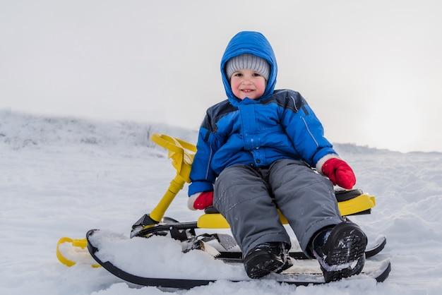 Un niño pequeño está sentado en una moto de nieve en invierno