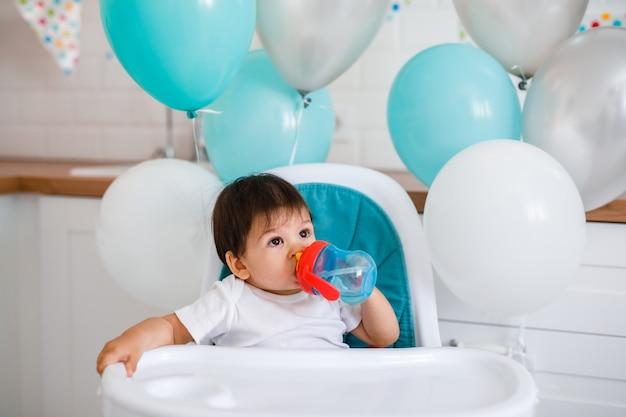Niño pequeño sentado en la silla alta en casa en la cocina blanca y bebiendo agua de una taza para sorber en el fondo con globos.