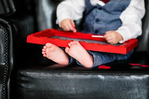 Niño pequeño sentado en el sillón con una imagen enmarcada en rojo en el día de san valentín; pequeños pies de primer plano