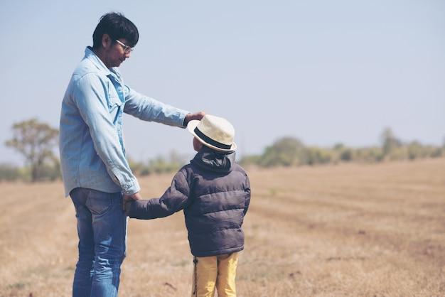 Niño pequeño está sentado sobre los hombros de su padre en el campo