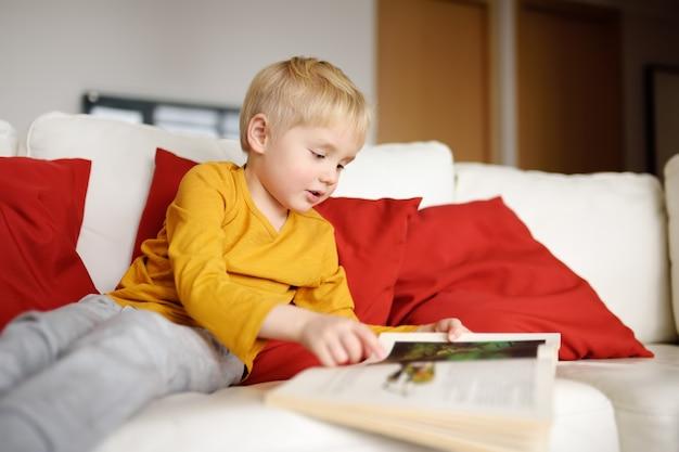 El niño pequeño se está sentando en casa en el sofá y está leyendo un libro. aprendiendo a leer.