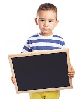 Niño pequeño serio sujetando una pizarra negra