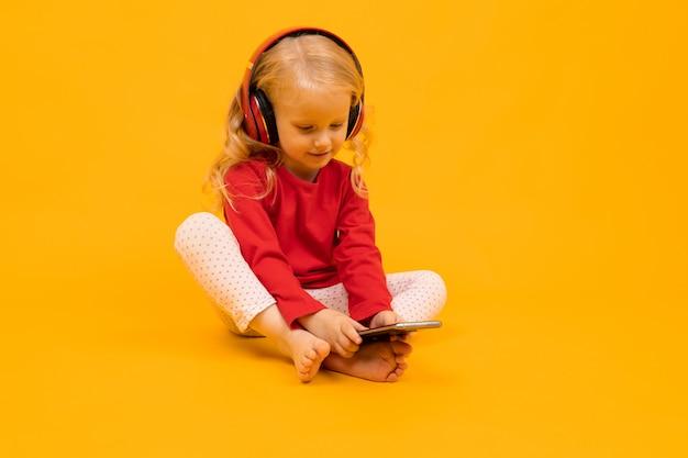 El niño pequeño se sienta en el piso con auriculares y se sienta en el teléfono sobre un fondo amarillo