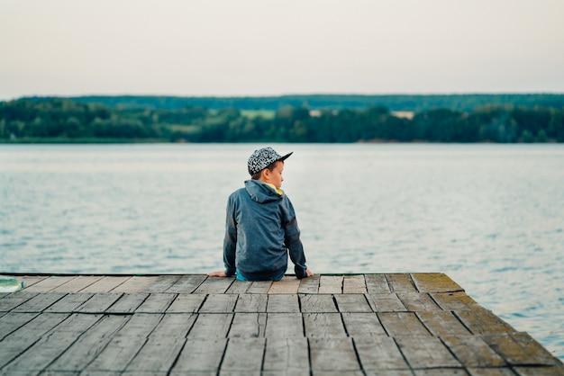 El niño pequeño se sienta en el puente cerca del lago. él está rodeado de una vista maravillosa.
