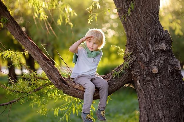 El niño pequeño se sienta en una rama de árbol y mira en la distancia.