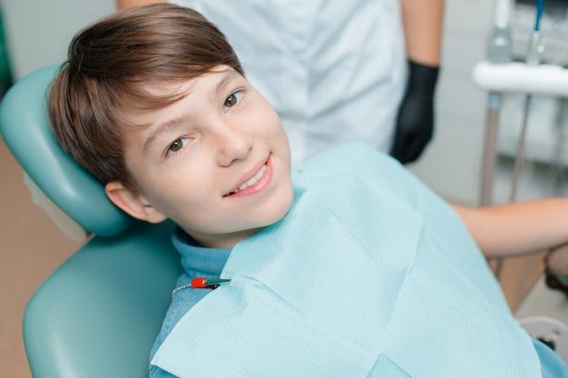 Niño pequeño en silla dental. paciente en el consultorio del dentista después del tratamiento.